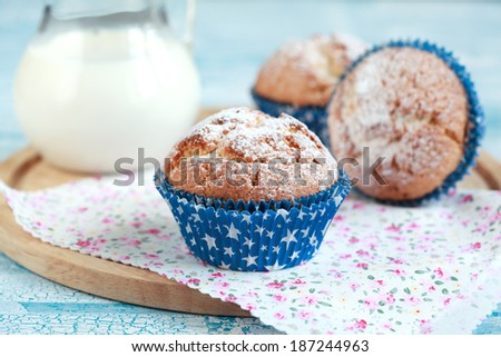 Close-up of three homemade orange muffins with a jug of milk, selective focus - stock photo