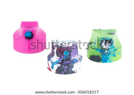 Close-up of three used painty colorful spray can nozzles isolated on white background. - stock photo