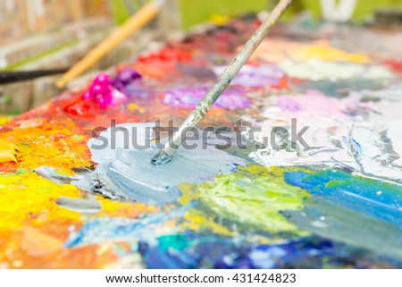 Close up of tiny paintbrush mixing colors on the multicolored palette of blended oil paints outdoors - stock photo