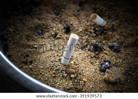 Close-up of Tobacco Cigarettes in ashtray with sand,unhealthy - stock photo