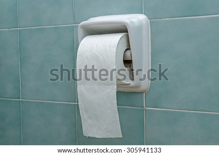 Close-up of toilet roll holder in bathroom - stock photo