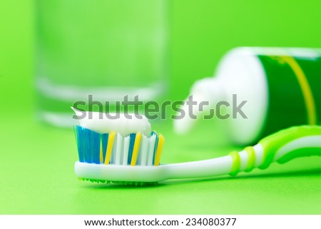 Close up of toothbrush and toothpaste tube on green background - stock photo