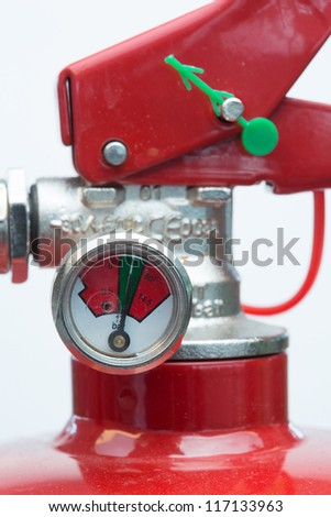 Close up of top of fire extinguisher with gauge - stock photo