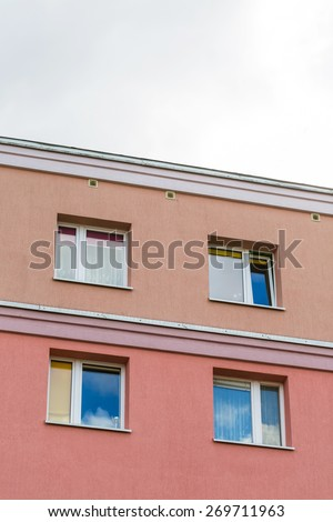 Close up of top part of block of flats building with blue sky. Architecture abstract. - stock photo