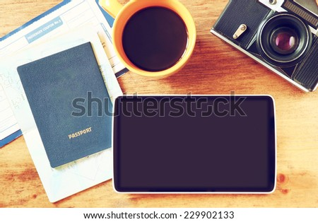 close up of top view image of tablet with empty screen, old camera, passport and flight boarding pass. - stock photo