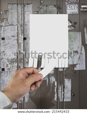 close-up of torn off empty advertising contact message with left hand - stock photo