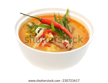 Close up of traditional Asian spicy soup with beef, chili and vegetables in white bowl, isolated on white, decorated with onion and chili pepper, restaurant dish, Tom Yum soup - stock photo