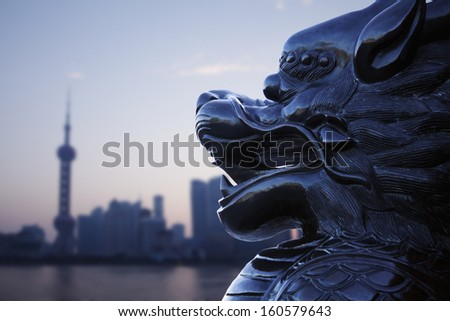 Close-up of traditional Chinese statue with Shanghai skyline in the background - stock photo