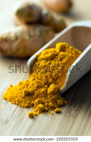 Close up of turmeric powder in wooden scoop - stock photo