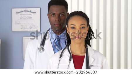 Close up of two African American doctors in hospital looking at camera - stock photo