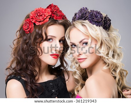 Close-up of two attractive, young ladies wearing flower alike accessories over grey background. - stock photo
