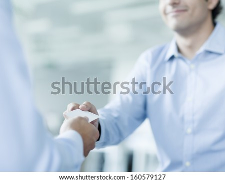 Close up of two businessmen exchanging business cards - stock photo