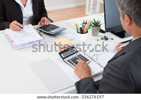 Close-up Of Two Businesspeople Calculating Financial Statement At Desk - stock photo