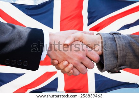 Close-up Of Two Businesspeople Shaking Hands In Front Of British Flag - stock photo