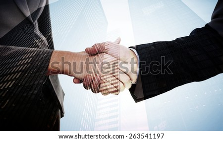 Close up of two businesspeople shaking their hands against low angle view of skyscrapers - stock photo