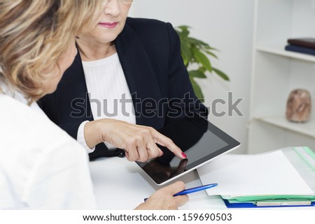 Close up of two   businesswomen around the table at work. - stock photo