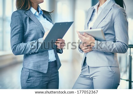 Close-up of two businesswomen interacting at meeting - stock photo