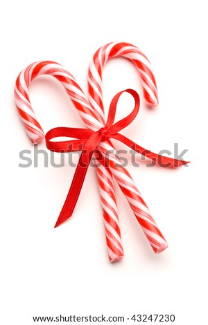 Close up of two candy canes tied with ribbon bow on white background - stock photo