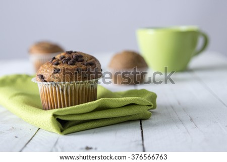 Close-up of two cupcakes decorated with chocolate chips  Green cup on background - stock photo