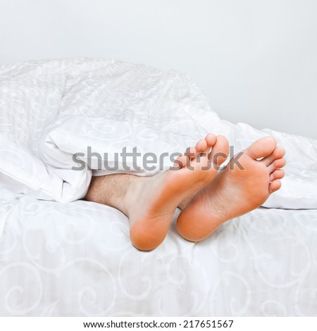 Close up of two feet in a bed  - stock photo