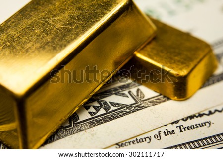 Close-up of two gold ingots and dollar banknotes - stock photo