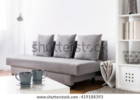 Close-up of two grey coffee cups on a white coffee table with blurred living room in the background - stock photo