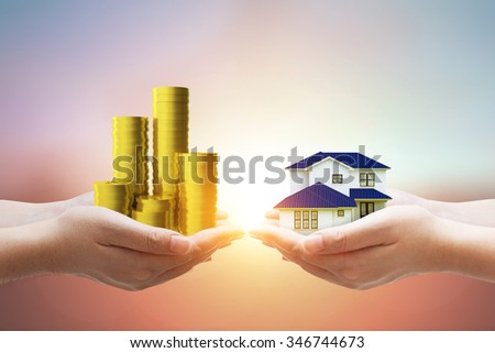Close up of Two Hand holding Money to Exchange Two Hand holding house model on pastel background - stock photo