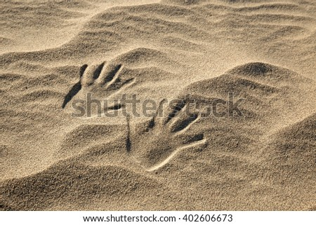 close up of two handprints on the sand - stock photo