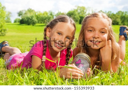 Close-up of two happy little nine years old girls hold jar with butterfly laying in the grass and showing big smile on happy faces - stock photo