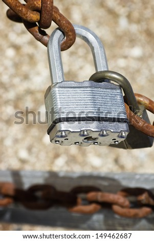 Close up of two locks lock and a rusty chain. Selective focus is on the larger lock.  - stock photo