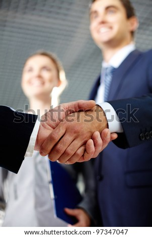 Close-up of two men hands shaking after signing contract - stock photo