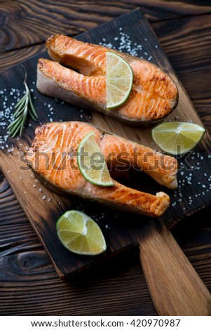 Close-up of two pan fried trout steaks with sea salt and lime - stock photo