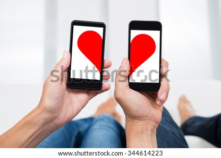 Close-up Of Two People Hands With Mobile Phones Showing Two Halves Of Heart Shape - stock photo