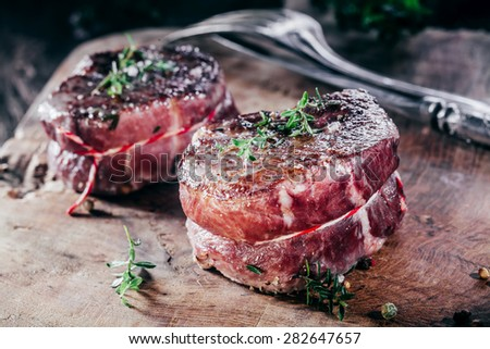Close Up of Two Rare Beef Steak Filets Seasoned with Fresh Herbs on Wooden Cutting Board with Cutlery - stock photo