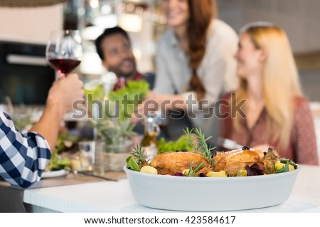 Close up of two roasted chickens with potatoes in a bowl on lunch table. Happy friends having lunch with two grilled chikens with salad. Group of people socializing at home.  - stock photo