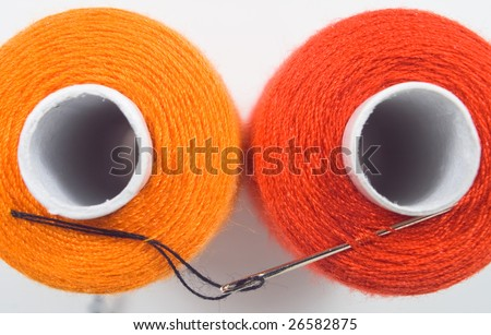 close up of two sewing spools with a needle - stock photo