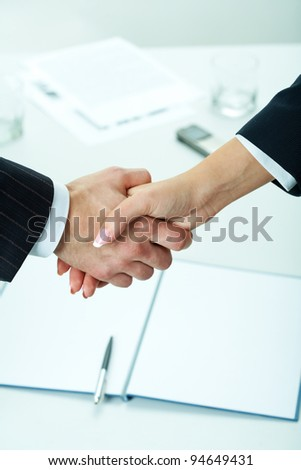 Close-up of two shaking hands with business documents on background - stock photo