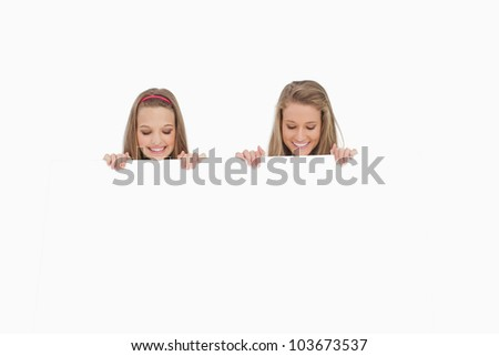 Close-up of two students behind a blank sign against white background - stock photo