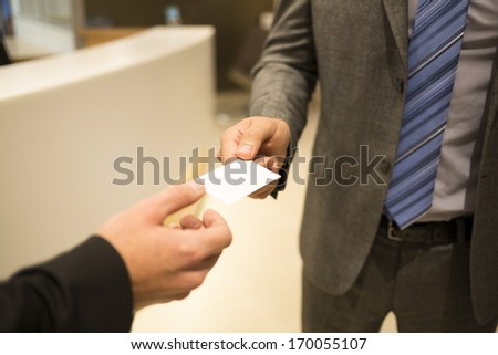 Close-up of two successful business executives exchanging a business card. - stock photo