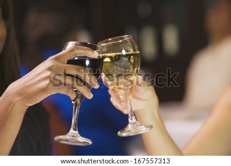 Close up of two women's hands toasting with wine glasses - stock photo