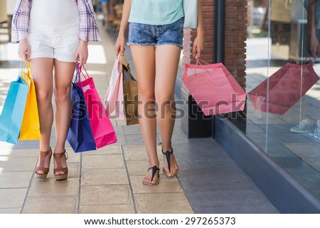 Close up of two women walking with shopping bags in shopping mall - stock photo