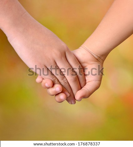 Close up of two young girls holding hands - stock photo