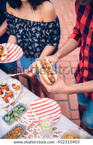Close up of unrecognizable young man holding an american hot dog in a outdoors summer barbecue with his friends - stock photo