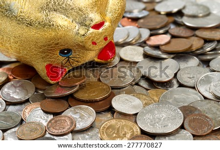 Close up of upside down piggy bank, focus on eye and nose, with loose change surrounding it. Financial concept of hard times.  - stock photo