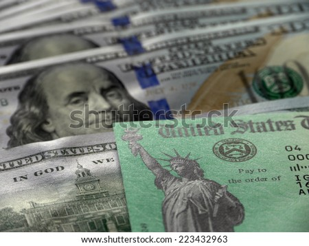 Close-up of USA tax return check and hundred dollar banknotes - stock photo