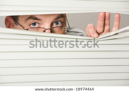 Close-up of venetian blind with male looking out of it - stock photo