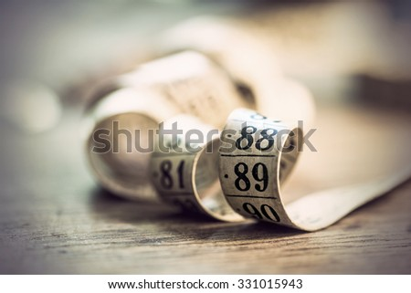 Close up of vintage tape measure on rough wooden surface - stock photo