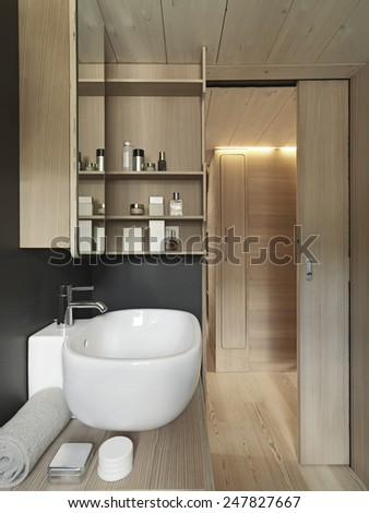 close up of washbasin in a modern bathroom with wood  sliding door and wood paneling - stock photo
