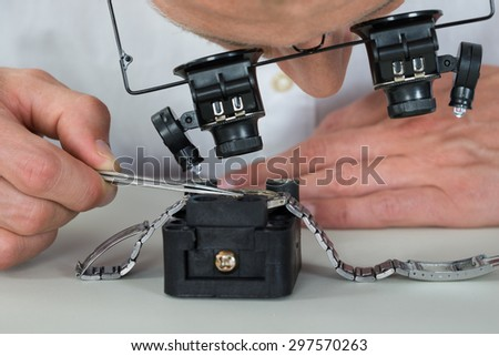 Close-up Of Watchmaker Using Loupe For Repairing Wrist Watch - stock photo