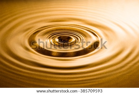 Close-up of water drop falling into water surface, creating ripple. - stock photo